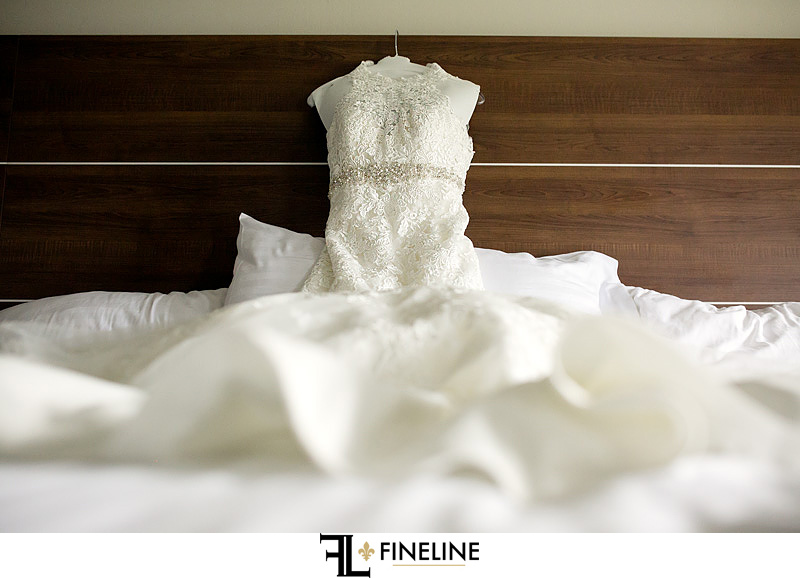 wedding dress hanging on bed