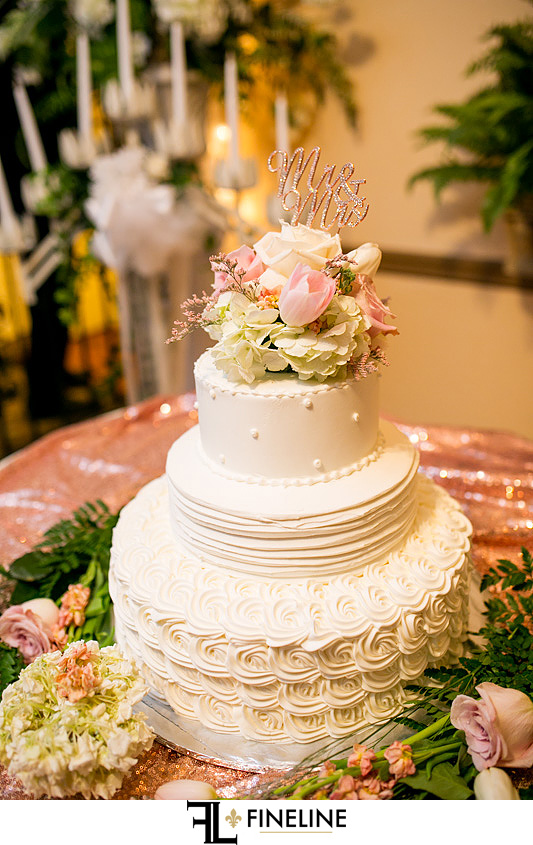 pink and cream wedding cake with rose gold accents