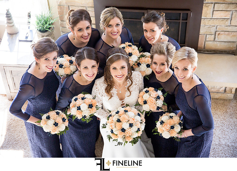 bridal party in navy blue with pink and white wood flowers